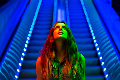 Portrait of illuminated young woman in front of blue lighted escalator looking up - p300m2028726 by VITTA GALLERY