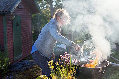 Woman having barbecue - p312m2145642 by Pernille Tofte