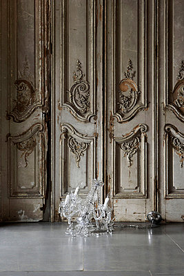 Glass chandelier on floor with ornate rococo style distressed wooden panelled wall - p3493197 by Jon Day
