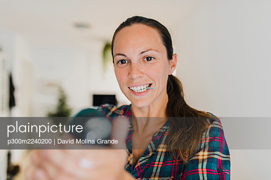 Mid adult woman holding screw in mouth while working with electric screwdriver at home - p300m2240200 by David Molina Grande