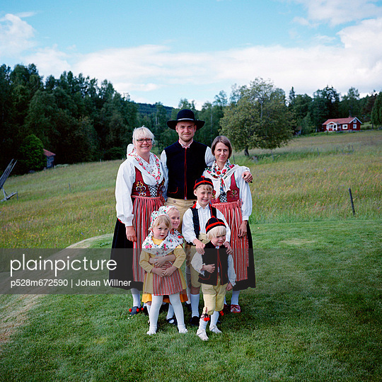 Family in traditional clothing standing on grass field, smiling - p528m672590 by Johan Willner