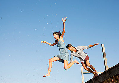 Exuberant couple jumping off dock - p1023m756137f by Sam Edwards