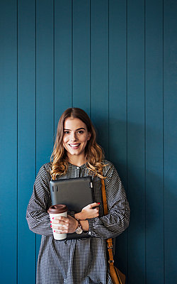 Portrait of smiling woman standing against wall in classroom - p1166m1210744 by Cavan Images