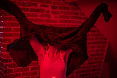 Junge Frau in rotem Licht - p1321m2141716 von Gordon Spooner