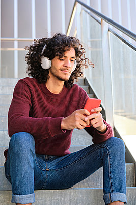 Young handsome man with headphones using smart phone while sitting on steps - p300m2273610 by Antonio Ovejero Diaz