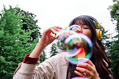 Young woman with headphones blowing bubbles in public park - p300m2293276 by Angel Santana Garcia