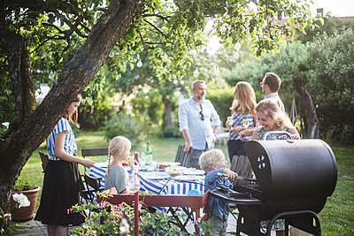 Boy preparing food on barbecue grill with mother while family enjoying at dining table in backyard party - p426m2138438 by Maskot