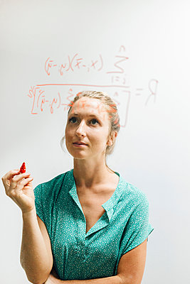 Young woman holding red marker pen gazing at complex equation on glass wall - p429m1504964 by JFCreatives