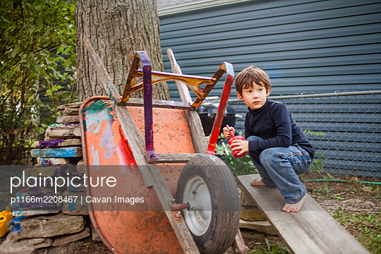 A small barefoot boy paints an old wheelbarrow with bright colors - p1166m2208467 by Cavan Images