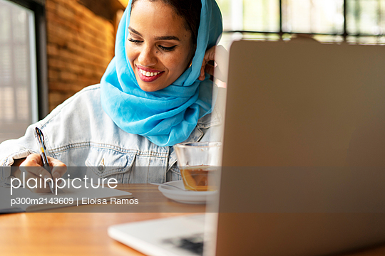 Businesswoman wearing turquoise hijab in a cafe and writing in notebook - p300m2143609 by Eloisa Ramos