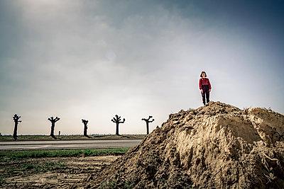 Girl on soil mound - p1402m2260804 by Jerome Paressant