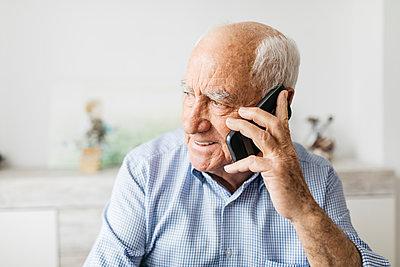 Happy senior man using smartphone at home - p300m2005560 by Josep Rovirosa
