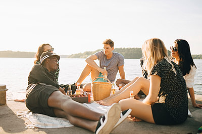 Multi-ethnic friends enjoying food and drink while sitting on jetty at lake against sky - p426m2097373 by Maskot