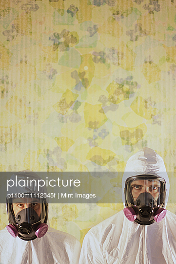 Two men wearing protective hazmat or clean suits in a room, with a background wall decorated with wallpaper.  - p1100m1112345f by Mint Images