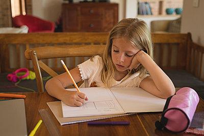 Girl doing her homework at home - p1315m1579135 by Wavebreak