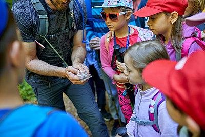 Man and kids with magnifying glass on a field trip - p300m1588102 von Zeljko Dangubic