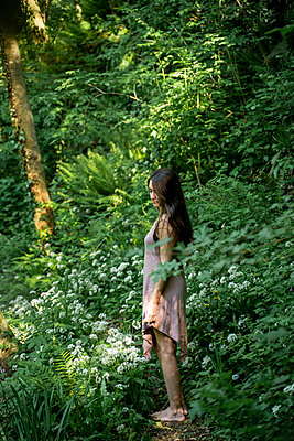 Young woman standing on a path in a lush forest, Garrotxa, Spain - p300m2113821 by VITTA GALLERY
