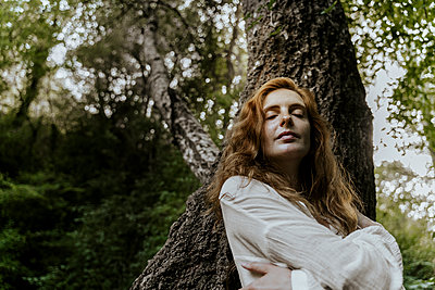 Young redhaired woman with closed eyes leaning on tree trunk - p300m2179915 by VITTA GALLERY