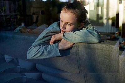 Serious girl on couch at home looking out of window - p300m2188164 by Stefanie Aumiller