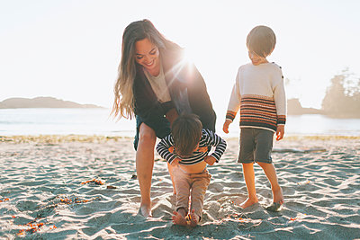 Woman playing with children at beach - p300m2213924 by Crystal Sing