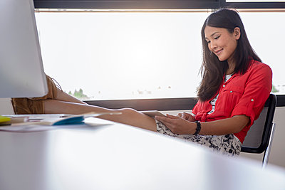 Smiling businesswoman using digital tablet with feet up on table while sitting at office - p300m2273723 by Buero Monaco