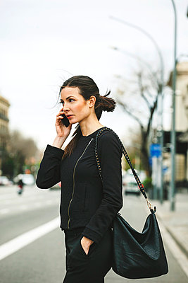 Spain, Catalunya, Barcelona, young black dressed businesswoman telephoning in front of a street - p300m981647f by Bonninstudio