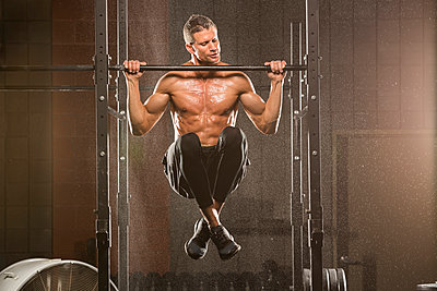 Caucasian man doing chin-up in gymnasium - p555m1303453 by Mike Kemp