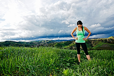 Mixed race athlete standing on rural hilltop - p555m1412196 by Peathegee Inc