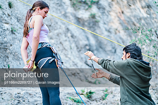 Monitor teaching a young girl with the climbing and mountaineering carabiners to climb. - p1166m2269727 by Cavan Images