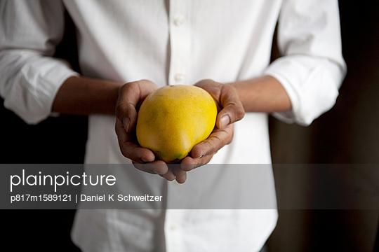 Mann hält eine frische Mango - p817m1589121 von Daniel K Schweitzer