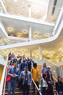 Business people descending stairs in modern lobby atrium - p1023m1583833 by Martin Barraud