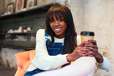 Portrait of smiling woman with coffee to go sitting on the couch in a loft - p300m1581093 by Bonninstudio