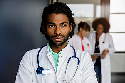 Young male professional standing with colleagues in background at hospital - p300m2281536 by Buero Monaco
