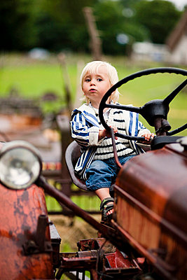 Portrait of baby boy on tractor - p312m695633 by Peter Rutherhagen