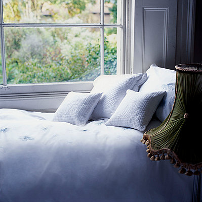 Single bed made with crisp white bed linen next to a window - p349m695195 by Emma Lee