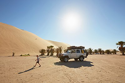 Boy walking on sand, Dune 7, Namib-Naukluft National Park, Africa - p429m1029771 by Stephen Lux
