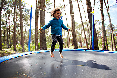 Mixed race girl jumping on trampoline - p555m1454090 by Granger Wootz