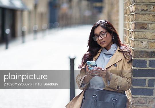 Woman using smart phone on sunny city street - p1023m2208379 by Paul Bradbury