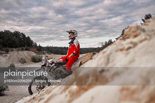 Motorbiker takes a break on motocross racing course - p1630m2206229 by Sergey Mironov
