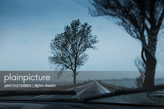 A Vehicle Driving On Straight Road In Rainy Season, Denmark   - p847m2104804 by Björn Abelin