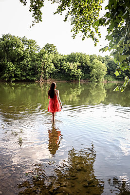 Woman in red dress standing in river - p1019m2099992 by Stephen Carroll