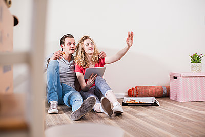 Young couple in new home sitting on floor with tablet - p300m1460040 by Uwe Umstätter