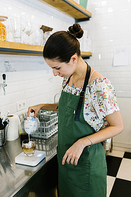 Barista pouring milk in coffee while standing in kitchen at coffee shop - p300m2227327 by Xavier Lorenzo