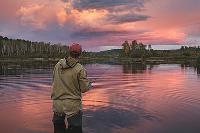 Rear view of man fishing in lake against cloudy sky at forest during sunset, Svobodniy, Amur, Russia - p301m1482490 by Vasily Pindyurin