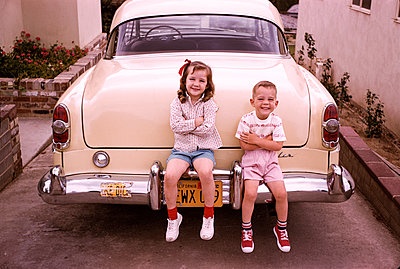 Caucasian brother and sister sitting on bumper of vintage car - p555m1444164 by PBNJ Productions