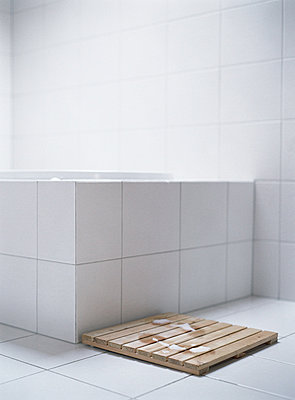 Wet footprints on wooden mat next to bath tub. - p6234397f by Matthieu Spohn