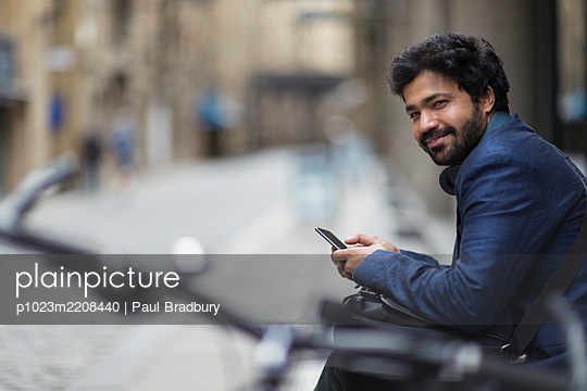 Portrait smiling businessman with smart phone on city street - p1023m2208440 by Paul Bradbury