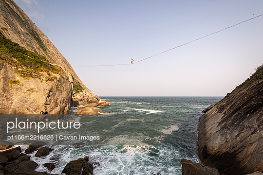 Beautiful view to highliner walking the line on rocky ocean shore - p1166m2216826 by Cavan Images