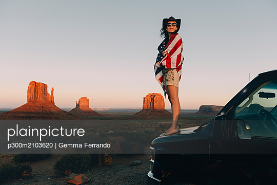 USA, Utah, Monument Valley, Woman with United States of America flag enjoying the sunset in Monument Valley - p300m2103620 by Gemma Ferrando