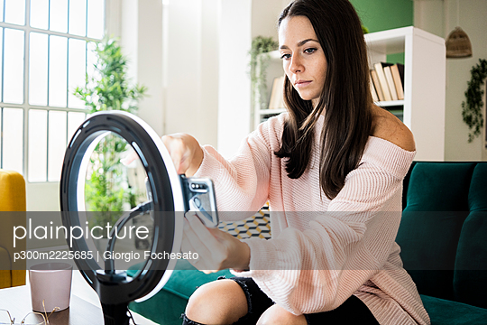 Beautiful female influencer sitting on sofa while adjusting smart phone on lighting equipment at home - p300m2225685 by Giorgio Fochesato
